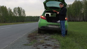Young man with broken car on the rural road takes triangle from car trunk stock footage