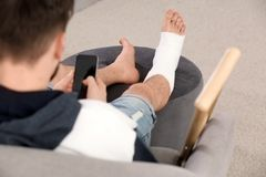 Young man with broken leg in cast using mobile phone royalty free stock photo