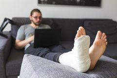 Young man with a broken leg on the sofa. Young man with a broken leg is sitting on the sofa at home stock photo