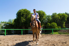 Young man on a brown-blond horse in the riding club Royalty Free Stock Photography