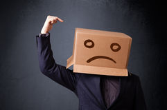Young man with a brown cardboard box on his head with sad face Stock Photos