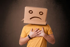 Young man with a brown cardboard box on his head with sad face. Young man standing with a brown cardboard box on his head with sad face royalty free stock photo