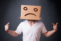 Young man with a brown cardboard box on his head with sad face Stock Photography