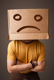 Young man with a brown cardboard box on his head with sad face Royalty Free Stock Image