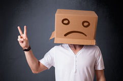 Young man with a brown cardboard box on his head with sad face Royalty Free Stock Photography