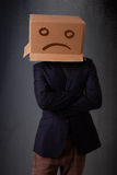 Young man with a brown cardboard box on his head with sad face Royalty Free Stock Images