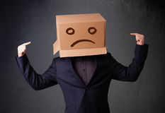 Young man with a brown cardboard box on his head with sad face Royalty Free Stock Photo