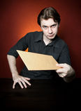 Young man with brown envelope. Royalty Free Stock Images