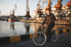 Young man with brown hair standing with bicycle and thoughtfully looking aside. Cool boy in down jacket on bicycle. Standing with sea port on the background Royalty Free Stock Photos