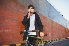 Young man with brown hair standing with classic bicycle and dreamily looking aside talking on his cellphone. Portrait of. Young man with brown hair standing with Royalty Free Stock Image