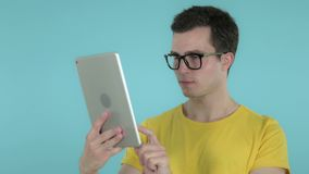 Young Man Browsing Interne on Tablet, Blue Background. The Young Man Browsing Interne on Tablet, Blue Background, high quality stock video