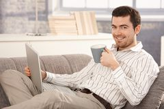 Young man browsing Internet at home smiling Royalty Free Stock Image