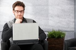 Young man browsing internet on laptop Royalty Free Stock Images
