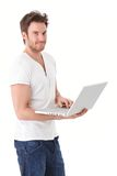 Young man browsing internet on laptop smiling Royalty Free Stock Images