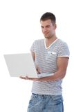 Young man browsing internet smiling Royalty Free Stock Images