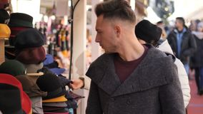 Young man browsing through products in open air market. Outdoor in a winter day, looking at hats and scarves stock footage