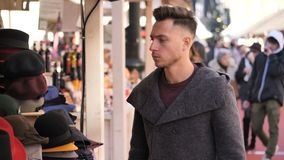 Young man browsing through products in open air market stock video
