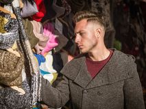 Young man browsing through products in open air market. Outdoor in a winter day, looking at hats and scarves stock image