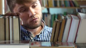 Young man browsing through the racks of books in a stock video