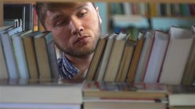 Young man browsing through the racks of books in a stock footage