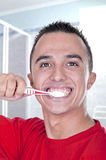 Young man brushing his teeth. In the bathroom Stock Photo