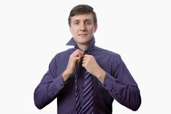 Young man brushing his teeth also looks on at watch on white background Royalty Free Stock Photo