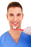 A young man brushing his teeth isolated on white background Stock Images