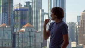 Young man brushing his teeth standing on a balcony with a view on a city center full of skyscrapers.  stock footage