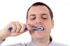 Young man Brushing teeth Stock Images