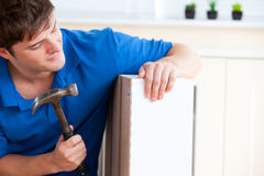 Young man building furniture using hammer and nail Royalty Free Stock Photos