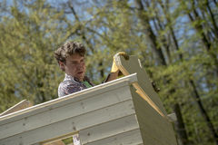 Young man building a garden hut Stock Photography