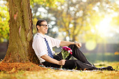 Young man with a bunch of flowers sitting on a grass Royalty Free Stock Photography