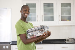 Young man with bundle of newspapers in kitchen, smiling, portrait Stock Photography