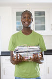 Young man with bundle of newspapers, smiling, portrait. Young men with bundle of newspapers, smiling, portrait Stock Photography