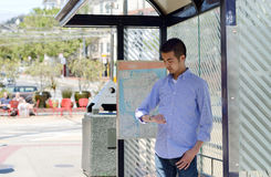 Young man at a bus stop. A young Asian man at a bus stop checking his watch as he waits Stock Photo