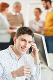 Young man in business apprenticeship. Young men in business apprenticeship makes a call with smartphone in office stock image
