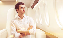 Young man in business class of a plane, toned Stock Photo