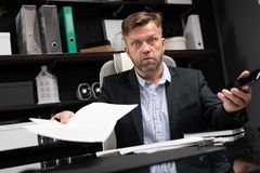 Young man in business clothes working at computer Desk with phone and documents. Handsome man in black jacket and light shirt looks at documents and is surprised stock images