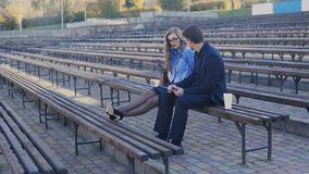 Young man and business lady are sitting on a bench in the park. The woman hurts her legs after a hard working day. Shot in 4k stock video