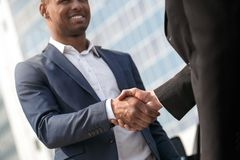 Young man and business partner standing near car shaking hands joyful close-up stock image