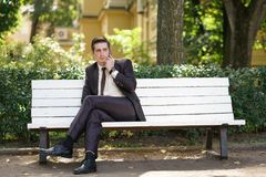 A young man in a business suit left the office and came to the Park. he sits on a white bench alone and talks on the phone. A tired man in a business suit left royalty free stock image