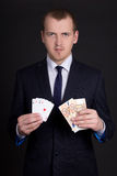 Young man in business suit with money and playing cards Royalty Free Stock Photo