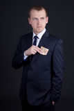 Young man in business suit putting euro banknote into pocket Royalty Free Stock Image