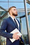A young man in a business suit with a tablet in his hands on the. Background of an office building. A successful office employee. Businessman in suit Royalty Free Stock Image