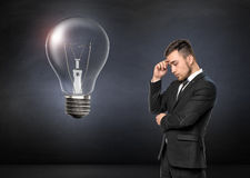 Young man in business suit thinking, on concrete wall background. Broken light bulb. Business concept Stock Photos