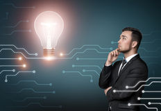 Young man in business suit thinking about idea, on concrete wall background. Shining light bulb. Business concept Stock Photos
