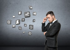 Young man in business suit, thinking about media, on concrete wall background. Business concept Stock Photography