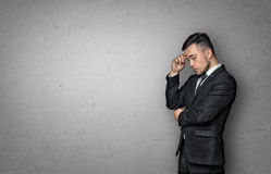 Young man in business suit, thinking about something, on concrete wall background. Business concept Royalty Free Stock Images