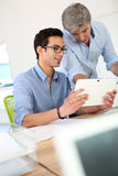 Young man in business training with tablet. Young men in business training school with teacher royalty free stock photo