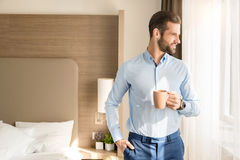 Young man business traveler hotel room accomodation. Young male business traveler hotel accomodation drinking coffee royalty free stock photography